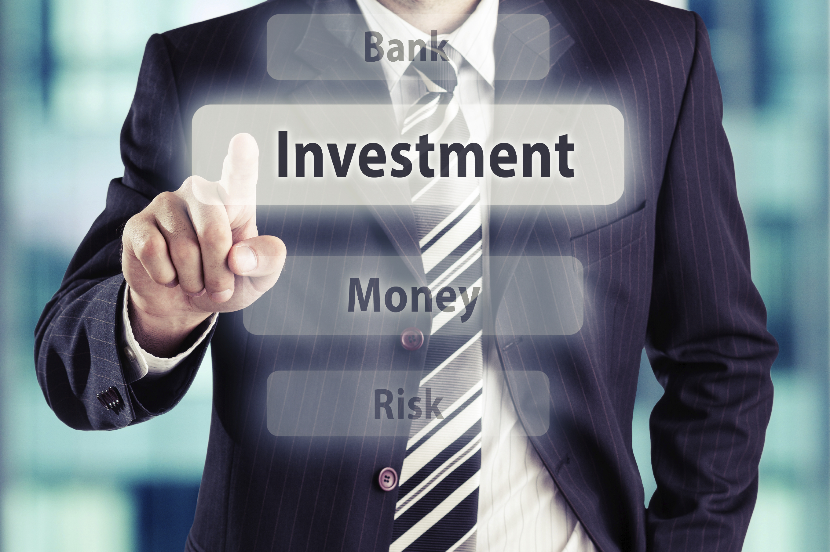 Business man pressing investment button at his office. Investment concept, toned photo.